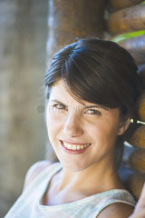 Woman leaning against wall  smiling  portrait