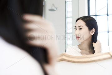 Woman looking in mirror  fixing her hair