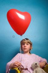 Berlin  Deutschland  ein Maedchen mit einem herzfoermigen Luftballon