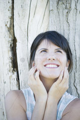 Woman leaning against tree trunk  looking up and smiling hopefully