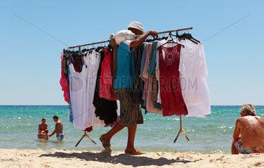 Santa Margherita di Pula  Italien  Mann traegt eine Kleiderstange mit T-Shirts am Strand entlang