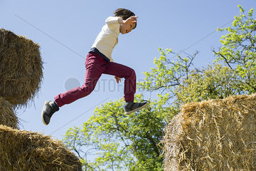 Boy jumping on haystacks