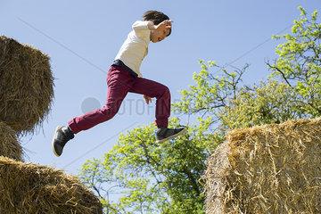 Boy jumping on haystacks