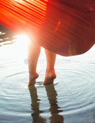Frau taucht Fuesse ins Wasser