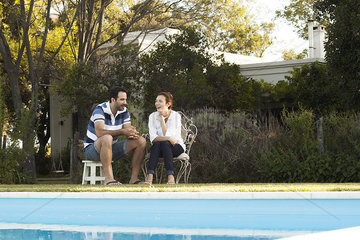 Couple relaxing together by backyard swimming pool
