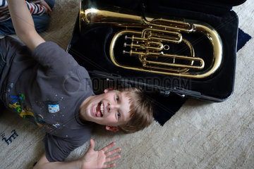 Berlin  Deutschland  Junge liegt vor einer Tuba auf dem Boden und macht Faxen