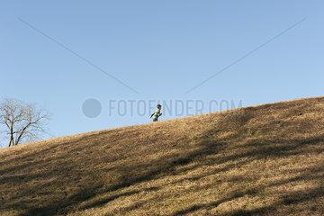 Child running on grassy hill