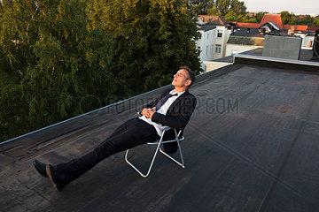 Geschaeftsmann entspannt auf dem Dach