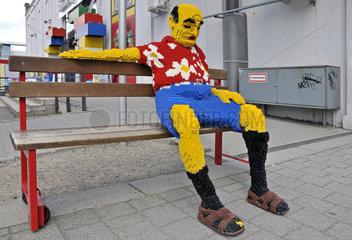 Legostein-Figur vor einem Lego-Geschaeft