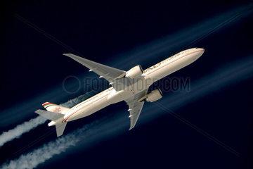 Etihad Airways Boeing 777-300ER im Flug mit Kondenzstreifen