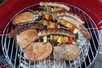 Grill mit Wuersten  Fleisch und Spiessen