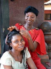Eine Frau laesst sich in der nigerianischen Hauptstadt Abuja die Haare flechten.