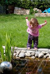 Kleines Maedchen am Gartenteich
