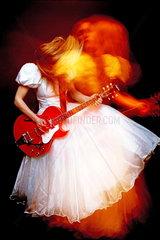 Braut im Brautkleid spielt E-Gitarre