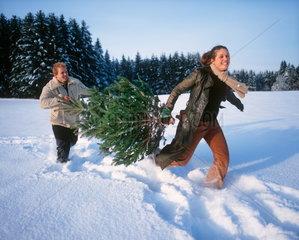 Junges Paar mit Weihnachtsbaum