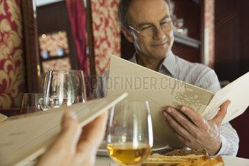 Mature man looking at menu in restaurant