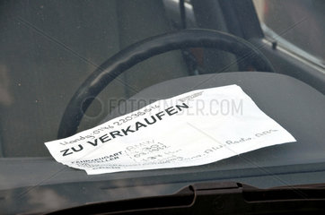 Angebotsschild fuer einen Gebrauchtwagen im Fond des Fahrzeugs.