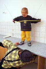 Kleiner Junge mit einem Massband