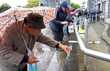 Pilger beim Abfuellen von Lourdes-Wasser