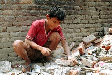 Junge zerschlaegt Steine auf einer Baustelle in Nepal