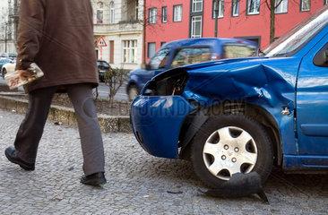 Berlin  Deutschland  Ein Mann geht an einem Unfallauto vorbei