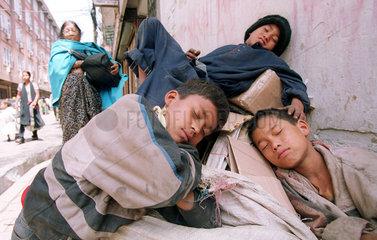 Drei Jungen ruhen sich auf Abfallsaecken aus in Kathmandu  Nepal