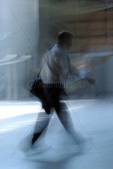 Schemenhafte Darstellung eines gehenden Mannes mit Tasche