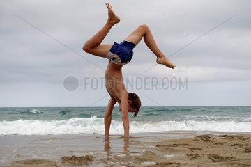 Noto  Italien  Junge macht am Strand von Calamosche einen Handstand
