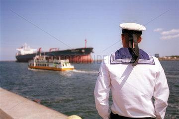 Matrose am Kai betrachtet die Schiffe in Rostock