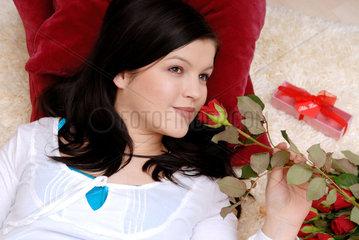 Berlin  eine junge Frau riecht an einer Rose