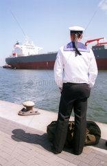 Matrose am Kai betrachtet ein Schiff in Rostock