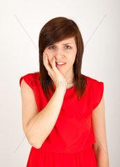 Die junge Frau hat Zahnschmerzen und haelt sich die Wange