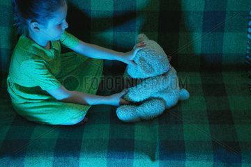 Little girl sitting on sofa with teddy bear
