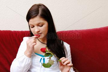 Berlin  eine junge Frau zerpflueckt eine Rose
