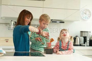 Kinder backen mit der Mutter einen Kuchen