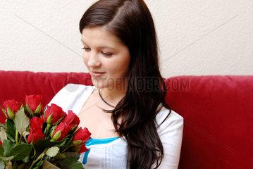 Berlin  eine junge Frau mit einem Strauss roter Rosen