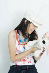Teenage girl holding stuffed toy  laughing