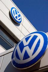 VW Firmenlogo vor einem Autohaendler