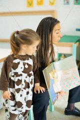 Teacher reading book aloud  child standing nearby