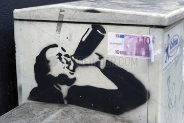 Graffiti eines Trinkers und Euro-Schein auf einer Trafostation