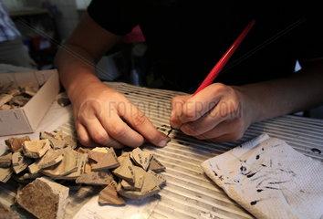 Archaeologische Zone in Koeln: Ein Mitarbeiter beschriftet gefundene Scherben mit abwaschbarer Tinte