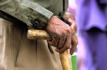Ein alter Mann stuetzt sich auf seinen Gehstock