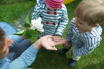 Kinder im Garten mit Regenwuermern