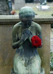 Freiburg  Deutschland  eine trauernde Grabfigur mit roter Rose auf einem Friedhof