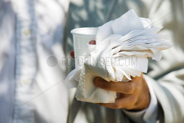 Hand holding disposable cup  paper napkins