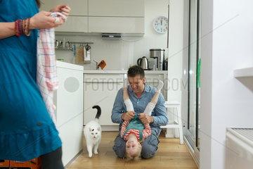 Vater spielt mit seiner Tochter in der Kueche