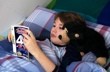 Lesender Junge im Bett