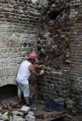 Archaeologische Zone in Koeln: Ein Steinmetz rekonstruiert eine roemische Mauer