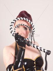 Frau im Latexkostuem haelt eine Peitsche