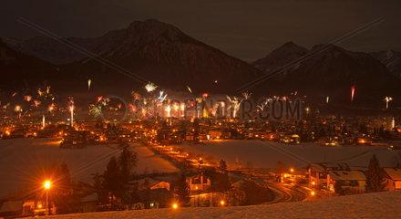 Silvesterfeuerwerk ueber Oberstdorf mit hell erleuchteter Schattenbergschanze  dahinter der Schattenberg  Allgaeuer Alpen